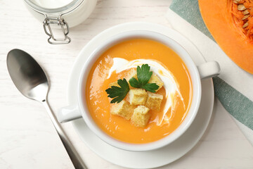 Delicious pumpkin soup in bowl served on white wooden table, flat lay