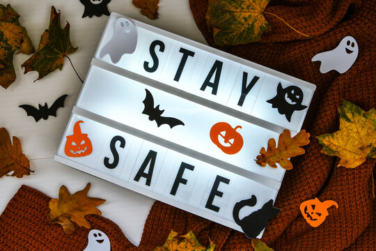 Stay safe. Text in white light box, with a background of sweater, dried leaves halloween autumn decoration. Coronavirus devices. Social distancing. Protection against pandemics