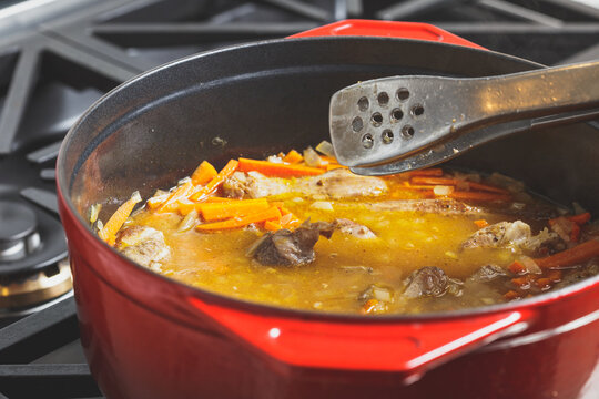 Pilaf cooking process at home in a red dutch oven