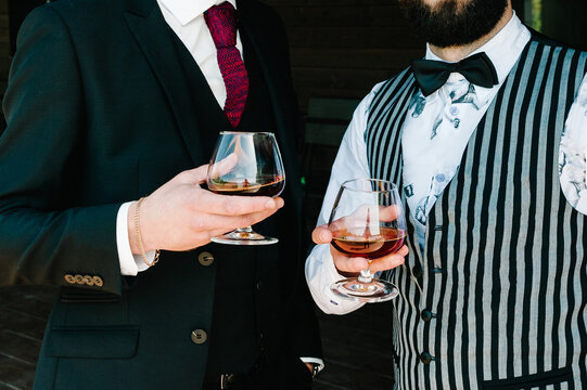 Cheers! Close up of two men celebrate and raise glasses of whiskey drink alcoholic beverage in the pub. Clink glasses of rum. Businessmen spending time together drinking brandy.
