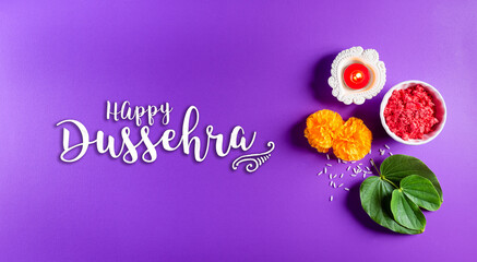 Happy Dussehra. Yellow flowers, green leaf and rice on purple pastel background. Dussehra Indian...