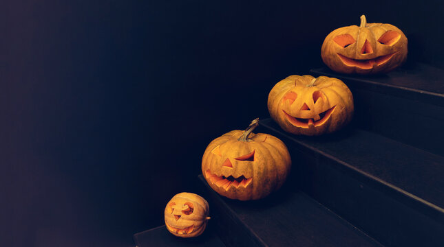 Halloween cutted pumpkins in every step of stairs, dark inside, black background, halloween decoration concept