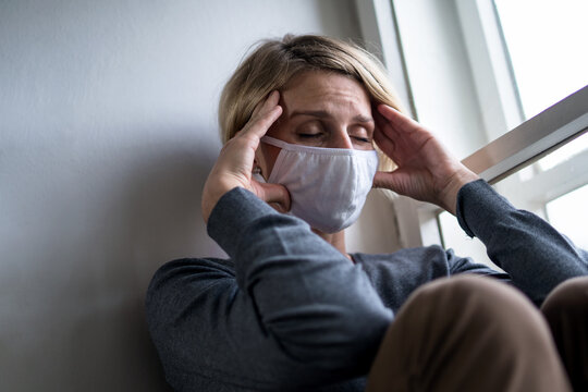 Woman indoors at home feeling stressed, mental health and coronavirus concept.