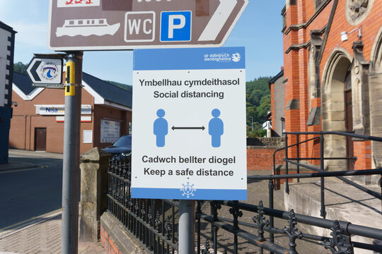 Social distancing notice on a public street in English and Welsh language  during the Coronavirus pandemic