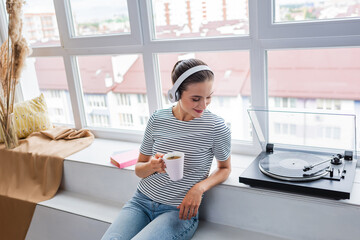 Woman with cup listening music in headphones near vinyl player on windowsill