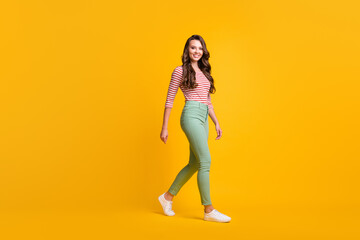 Photo sur Plexiglas Dinosaurs Full length body size side profile photo of girl with curly hair hurrying up smiling isolated on vivid yellow color background