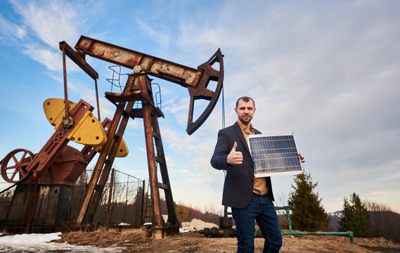 Businessman holding portable solar panel, showing approval gesture, standing on territory of oil field with pump jack, sky on background. Concept of petroleum industry and alternative source of energy