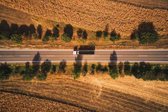 Top view aerial photo of truck on the road through plain landscape countryside