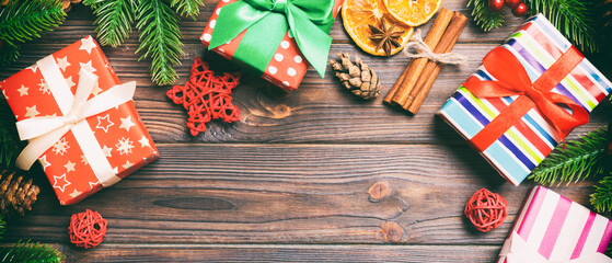Wall Mural - Top view of Banner Christmas background made of fir tree, gifts and other decorations on wooden background. New year holiday concept with copy space