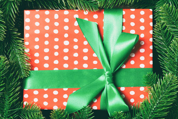 Wall Mural - Top view of gift box decorated with a frame made of fir tree on wooden background. New Year present time concept