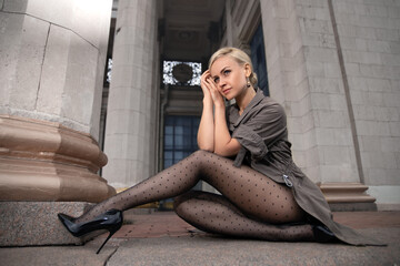 Photo sur Plexiglas Dinosaurs Beautiful blonde woman with perfect legs in pantyhose posing outdoor at the autumn street in the lights of the setting sun.