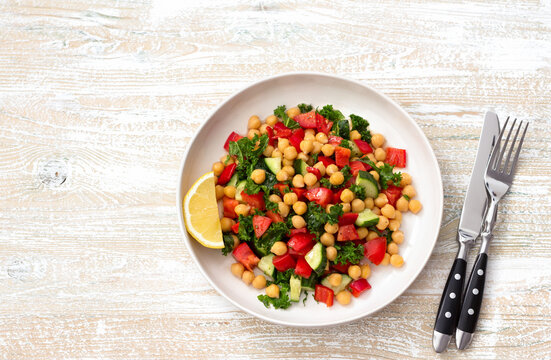 Healthy vegan salad with chickpeas, tomatoes, cucumbers, bell peppers and kale on light wooden background, flat lay, space