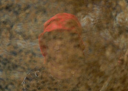 A farmer is seen through paddy rice grains while she dries them in the sun, after the harvest in Bhaktapur