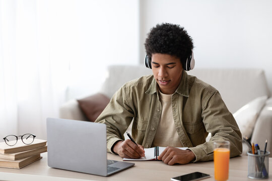 Studying from home. African American teenage guy in headphones writing down info during online lecture indoors