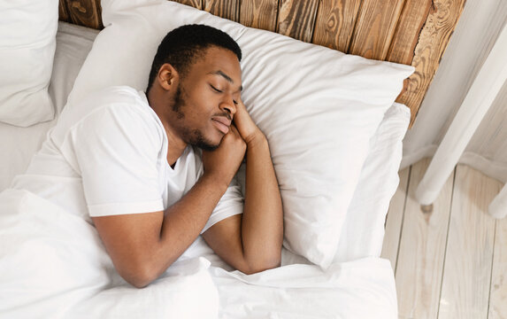African American Man Sleeping Peacefully In Comfortable Bed At Home