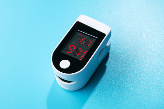 White new pulse oximeter on a blue table
