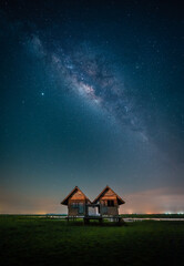 Wall Mural - Landscape image of milky way over the abandoned twin house near Chalerm Phra Kiat road in Thale Noi, Phatthalung, Thailand