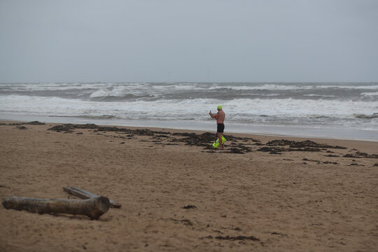 A lone swimmer uses a phone out of the water during the stormy seas at Longsands, in Tynemouth