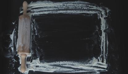 Fototapeta Wałek do ciasta z mąką na ciemnym czarnym tle do pieczenia, widok z góry, miejsce na tekst, menu, przepis. obraz