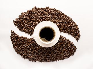Plano cenital de una taza de café caliente americano con granos tostados de café sobre la mesa formando la figura de un grano de café fotografía creativa