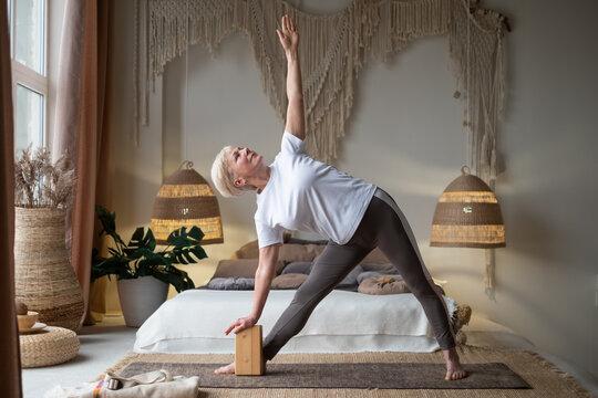 Senior woman practicing yoga, stretching in Utthita Trikonasana exercise, extended triangle pose