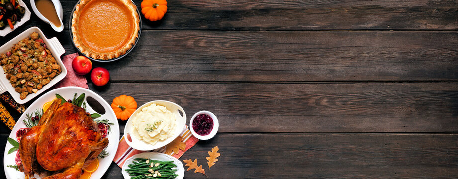 Traditional Thanksgiving turkey dinner. Top down view corner border on a dark wood banner background with copy space. Turkey, mashed potatoes, dressing, pumpkin pie and sides.