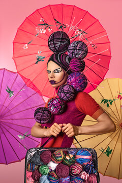 Portrait of an Asian woman with wool hair and makeup, holding a bag of wool balls in front of handcrafted umbrellas