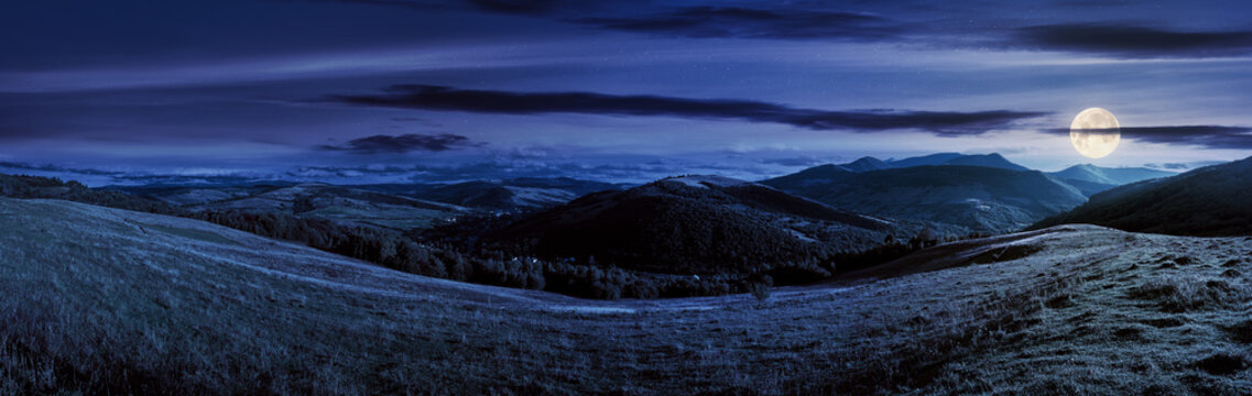 mountainous countryside landscape at night. panorama of a grassy rural field on the hill in full moon light. village in the distant valley. clouds on the sky