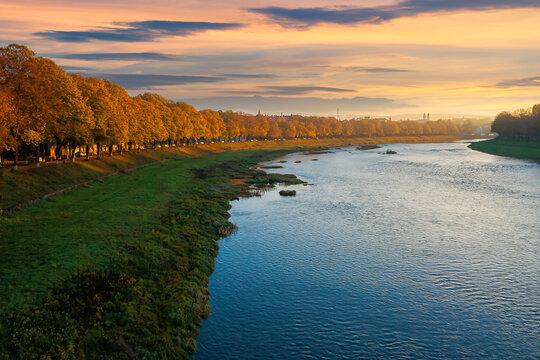 river uzh at sunrise. beautiful cityscape autumn scenery. linden alley in fall color in morning light. location uzhgorod, ukraine