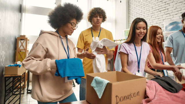 Happy young volunteers group sorting, packing clothes in cardboard boxes, Diverse team working together on donation project indoors