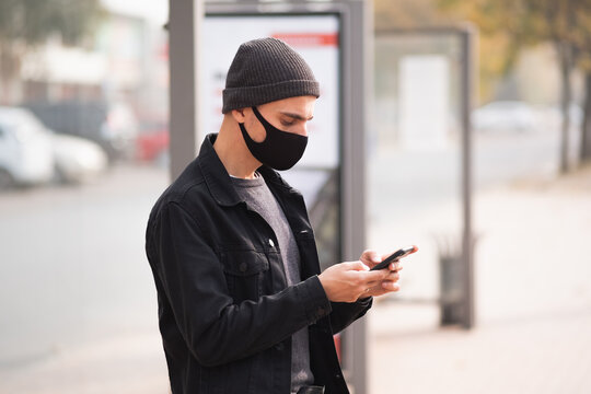 Man in mask with a cell phone at a bus stop. Millennial using smartphone at public place, covid time
