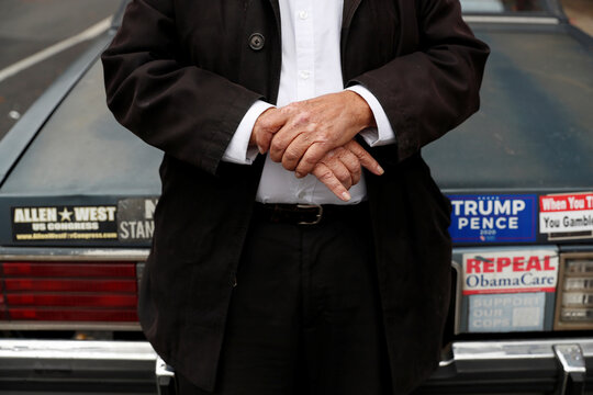 Jack Sandhaus, 83, poses with his hands closed behind his car as the spread of coronavirus disease (COVID-19) continues in the Park Slope section of the borough of Brooklyn in New York