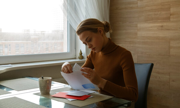 Attentive woman taking letter from envelop sitting at table