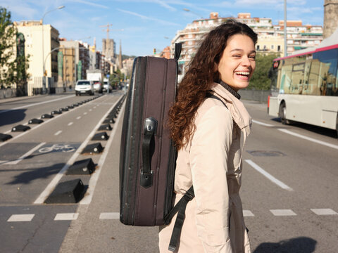 Young woman with instrument case in the city