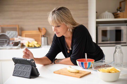 Woman having breakfast and using her tablet