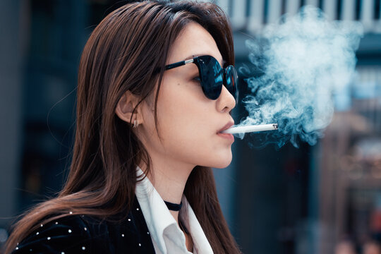 fashion woman smoking in city street