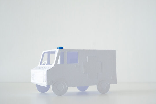 Stock photo of a little paper ambulance on a plain white background