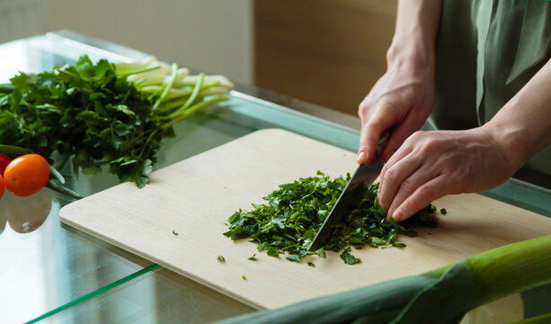 Crop woman cutting herbs for salad