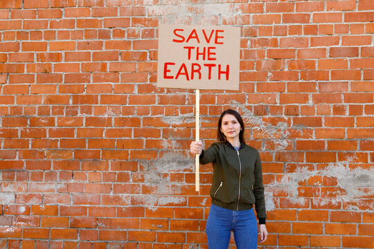 Young woman showing ecological banner against brick wall