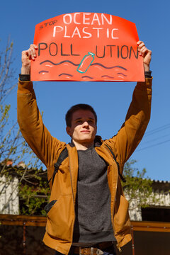 Young man with ecological placard on street