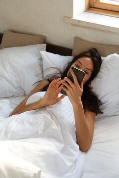 Pensive young woman using with interest smartphone while relaxing in bed at home