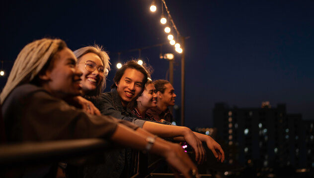 Group of friends looking at night sky from a balcony
