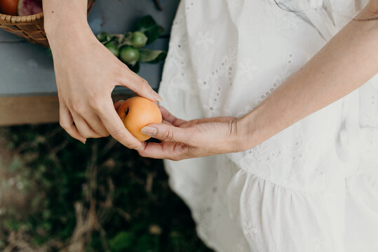 Petite Filipino woman wearing a white lace dress holding an apricot sitting on an old porch