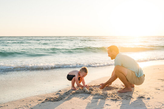 Uncle and nephew dig in the sand
