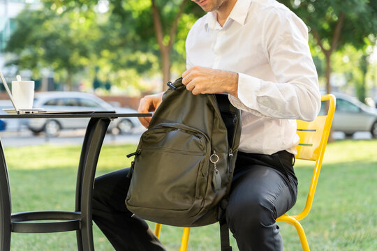 Businessman zipping backpack while sitting on chair at sidewalk cafe