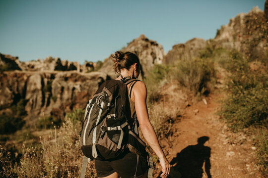 Woman with backpack hiking in forest