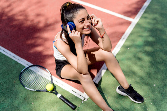 Smiling female tennis player listening music while sitting on floor in court
