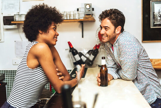 Smiling man holding beer bottle flirting with female bartender while standing at bar counter