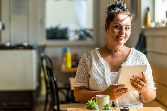 Smiling voluptuous woman using digital tablet while sitting in coffee shop