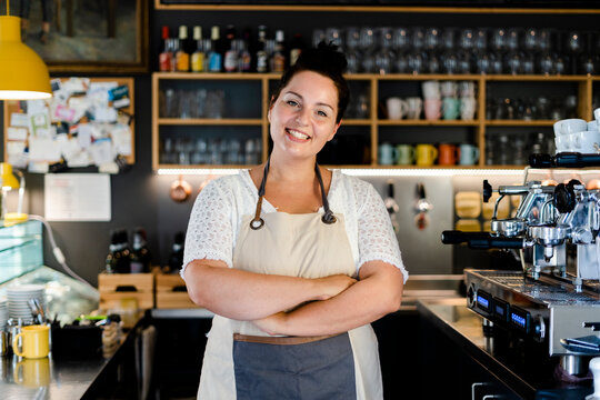 Smiling female barista with arms crossed standing in coffee shop